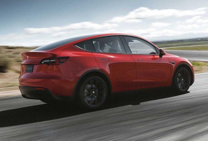 Tesla Model Y auto rossa vista posteriore dinamica su strada sfondo paesaggio